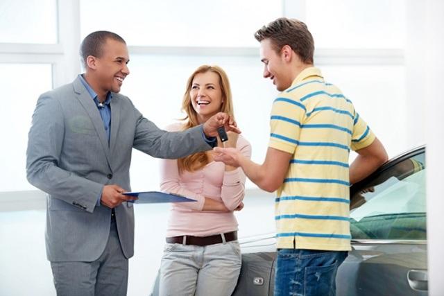 молодая пара покупает авто в кредит в автосалоне