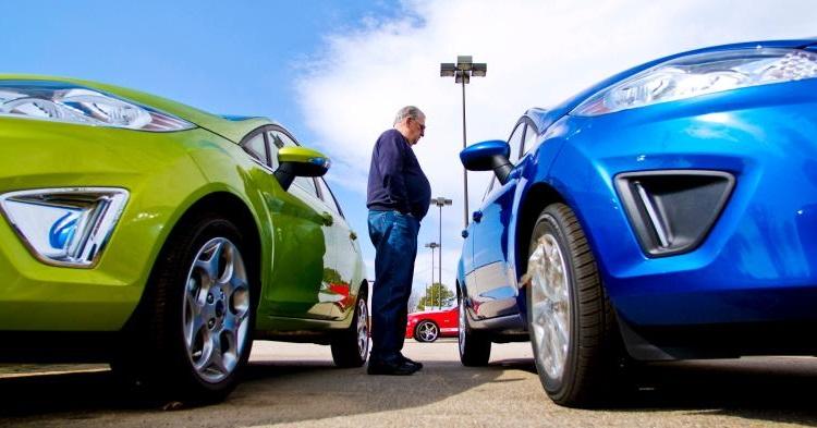 мужчина выбирает, какое из двух авто купить