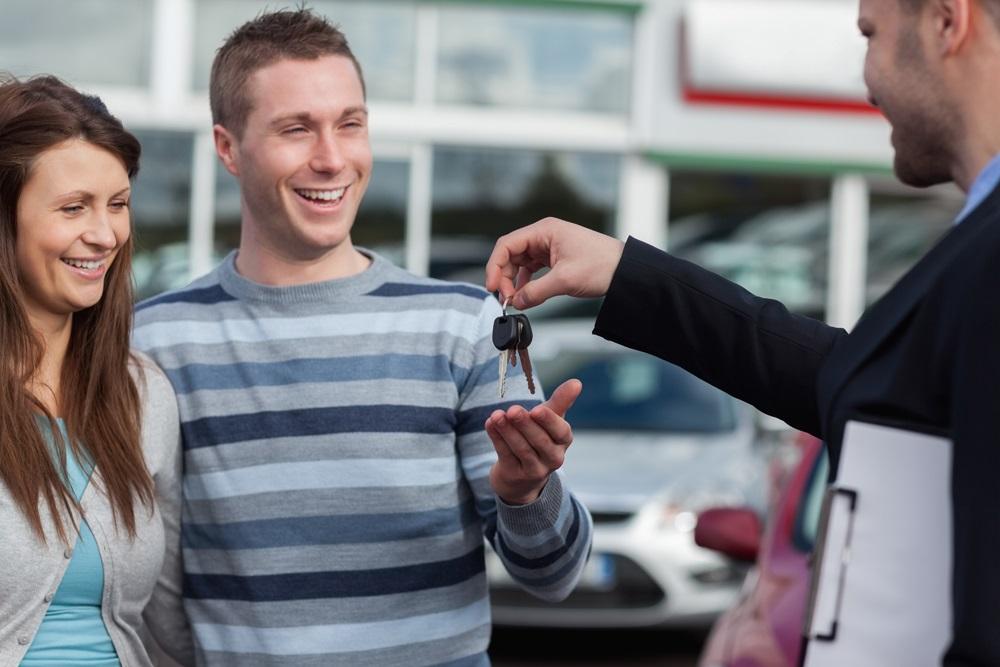 пара получает ключи от купланного в кредит автомобиля